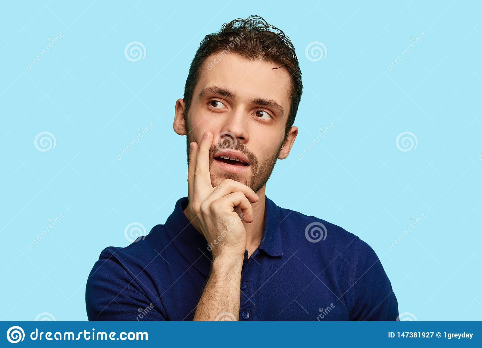 Thoughtful man standing with hand on chin and looking away isolated over blue background