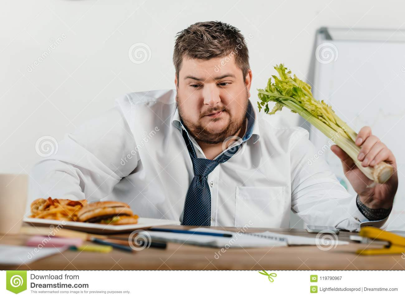 thoughtful overweight businessman choosing healthy or junk food at workplace