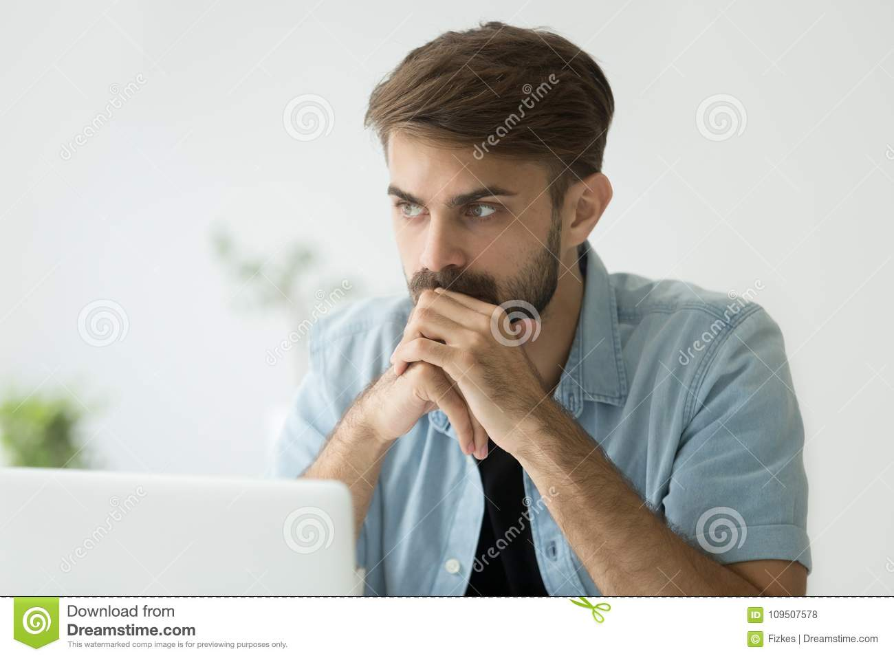Thoughtful serious man lost in thoughts in front of laptop