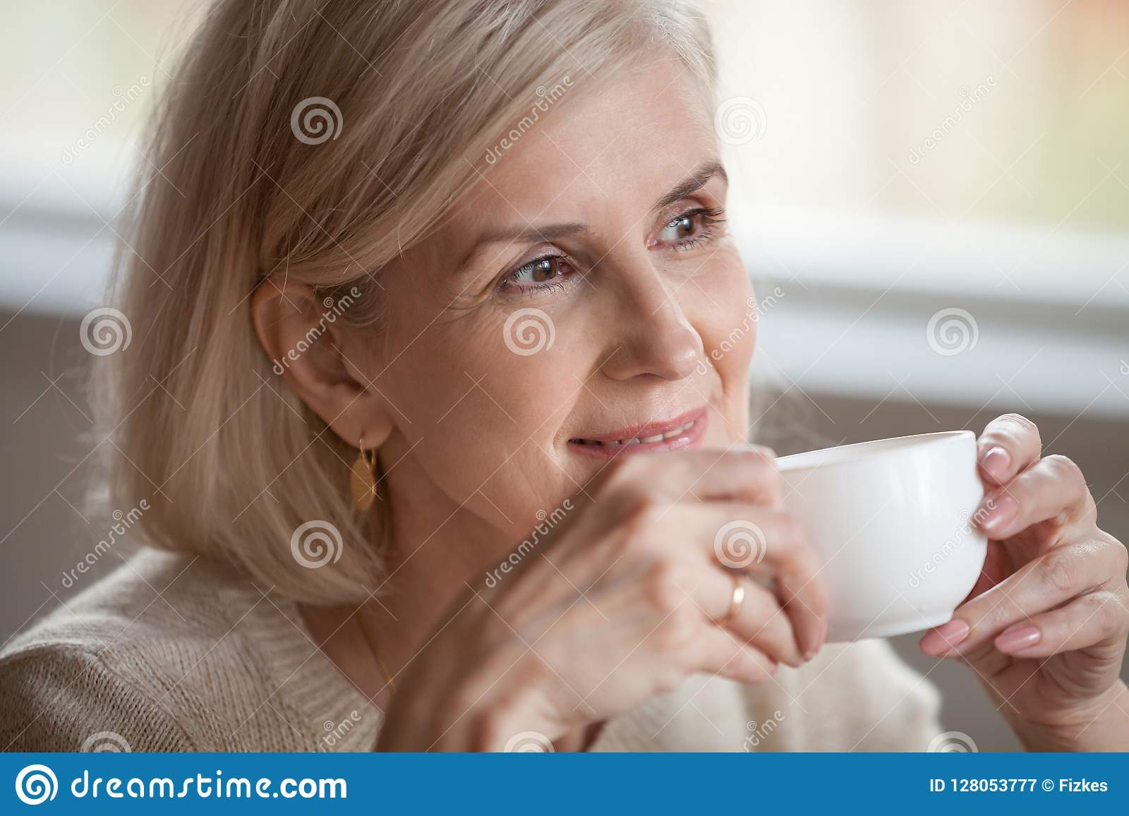 Thoughtful smiling middle aged woman looking away dreaming drink