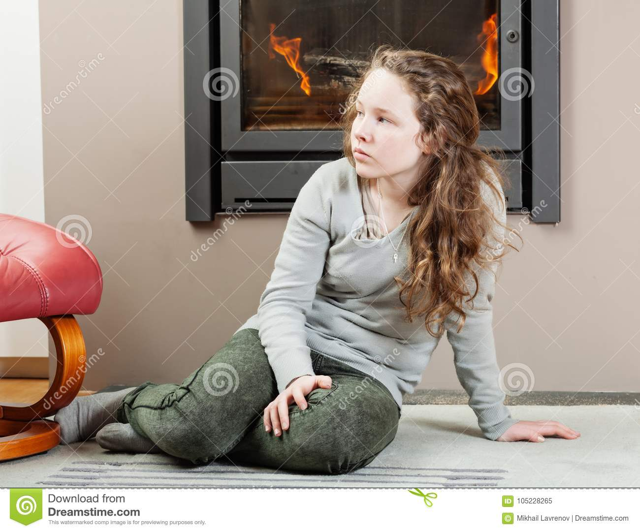 Thoughtful teenager girl sitting near fireplace