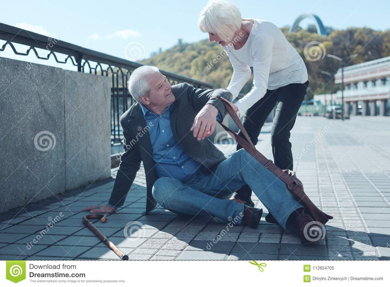Thoughtful woman helping mature stranger to stand up