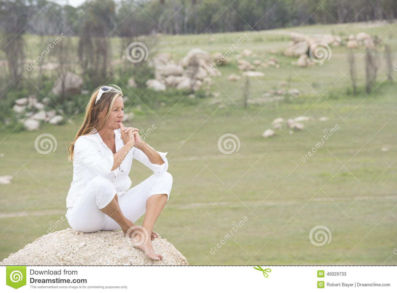 thoughtful woman outdoor sitting on rock stock image - image of