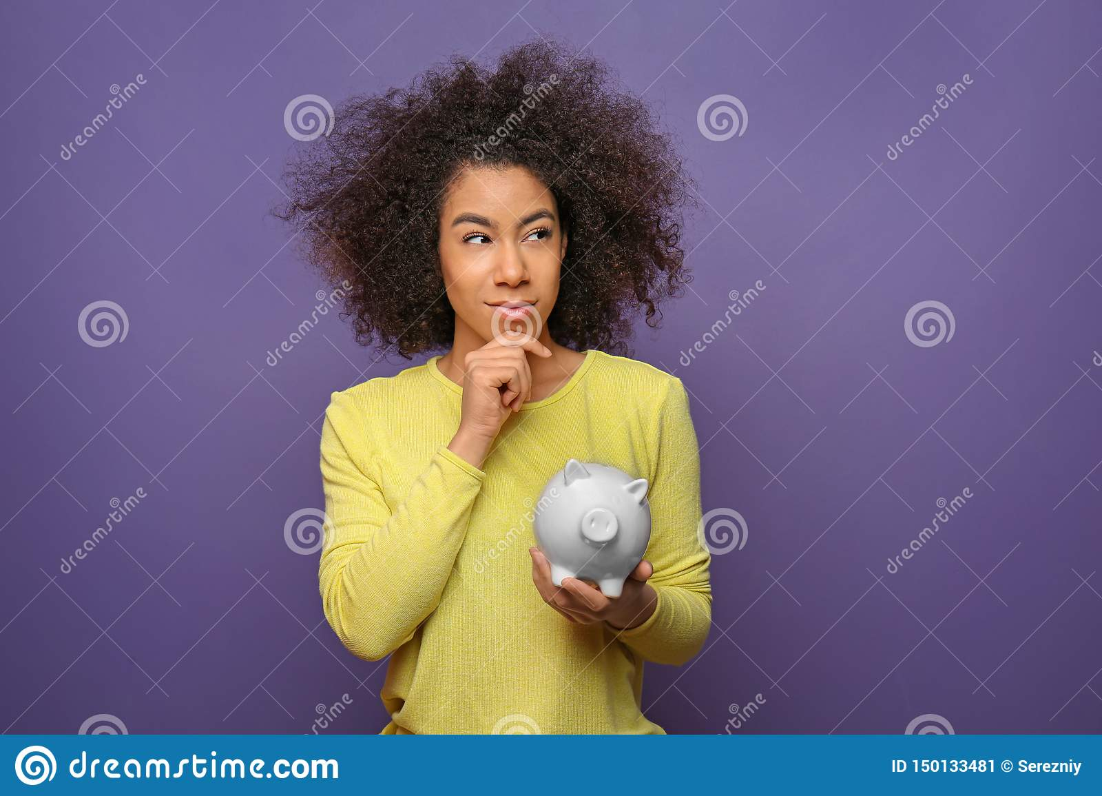 Thoughtful young African-American woman with piggy bank on color background. Savings concept