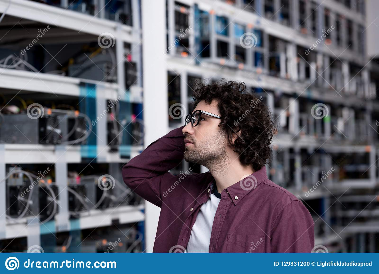 Thoughtful young computer engineer looking at cryptocurrency mining farm stock photo