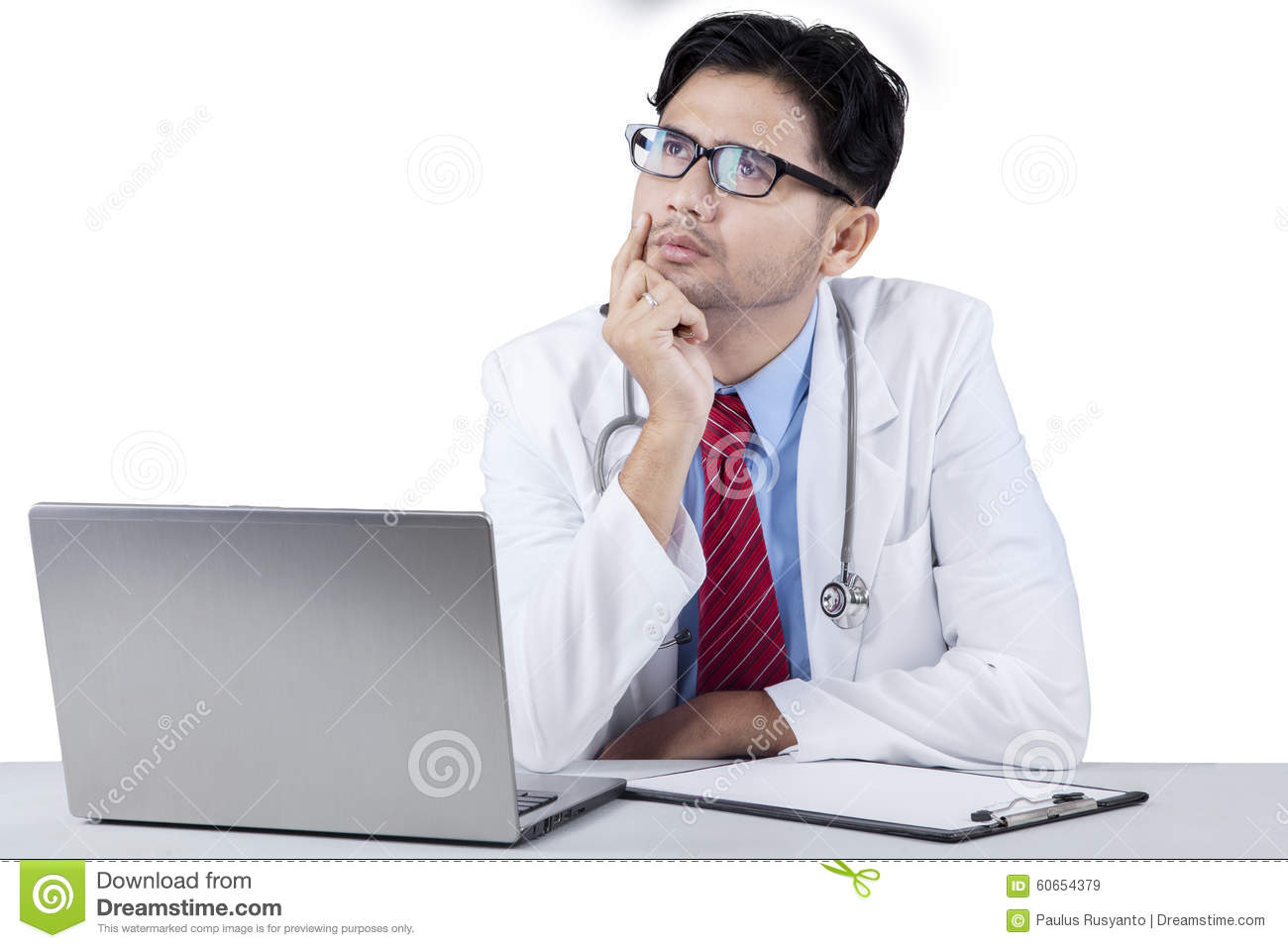 Thoughtful young doctor looking upward