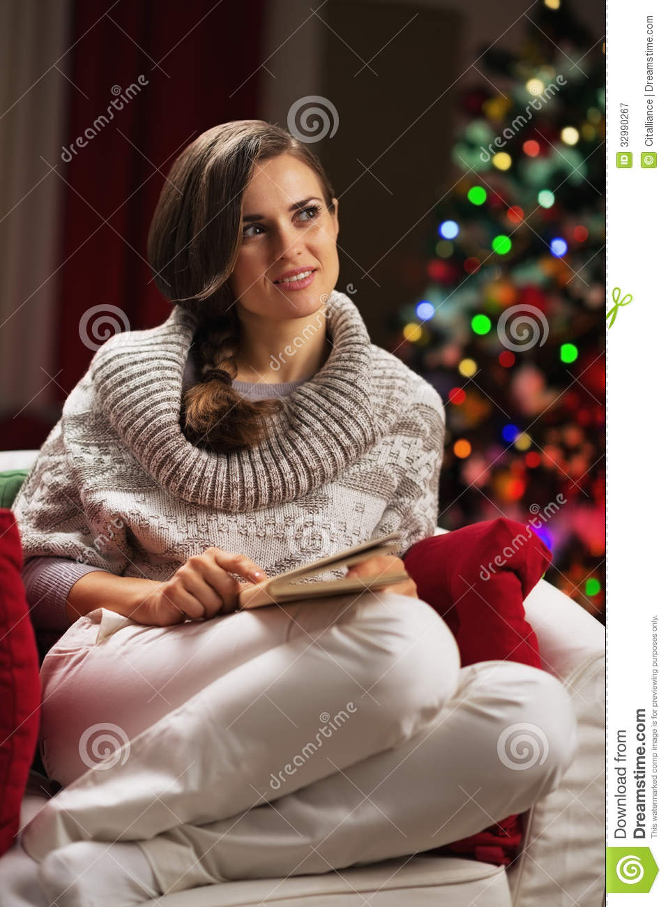 Thoughtful young woman sitting in armchair near christmas for Sitting in armchair