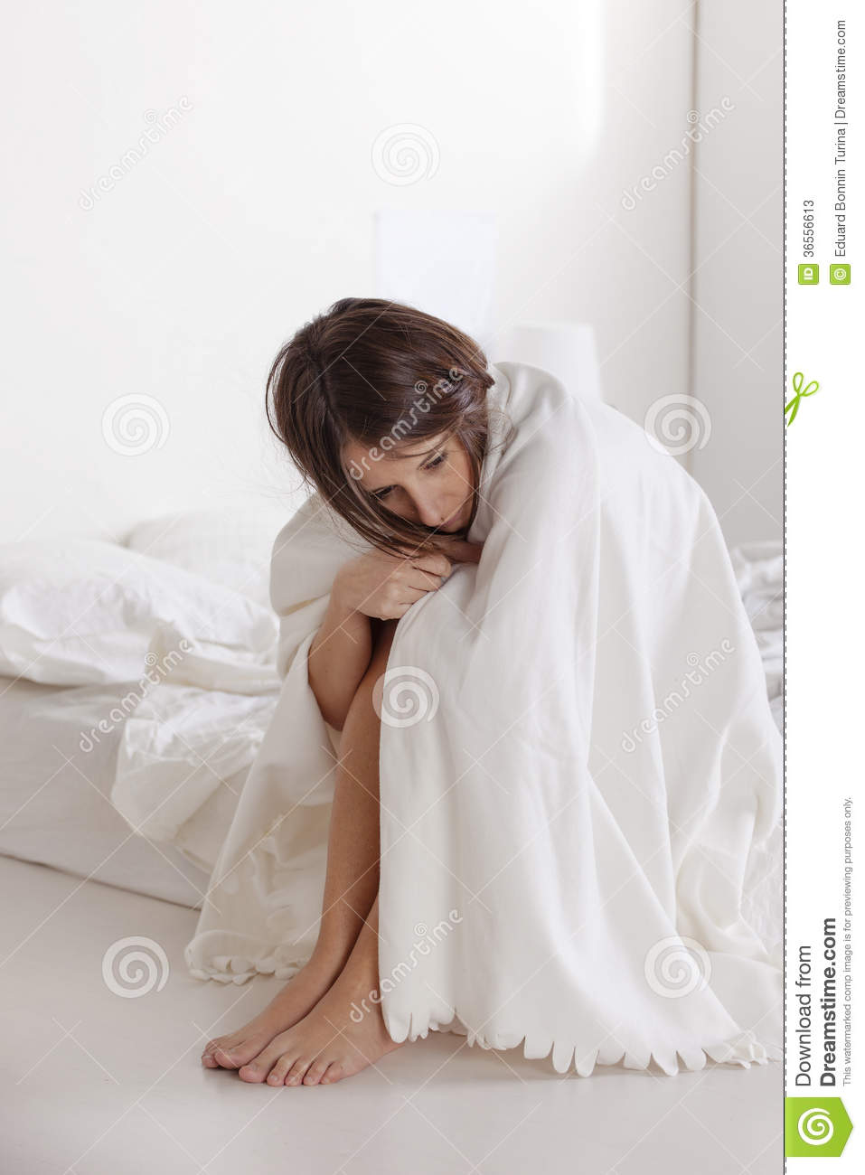 Thoughtful young woman sitting on white bed.