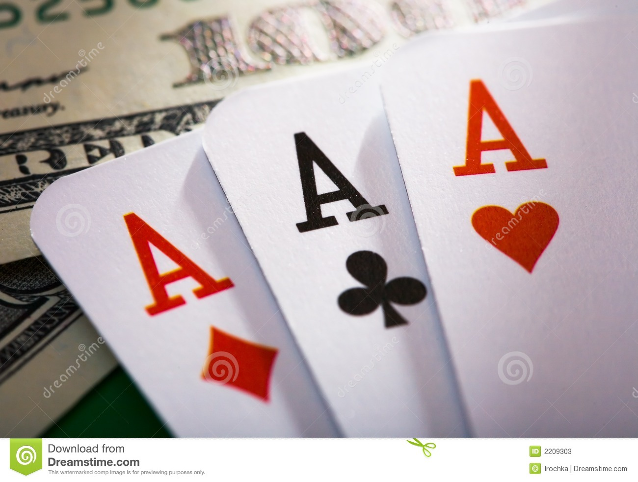 Closeup of three playing cards aces and one hundred dollar bills