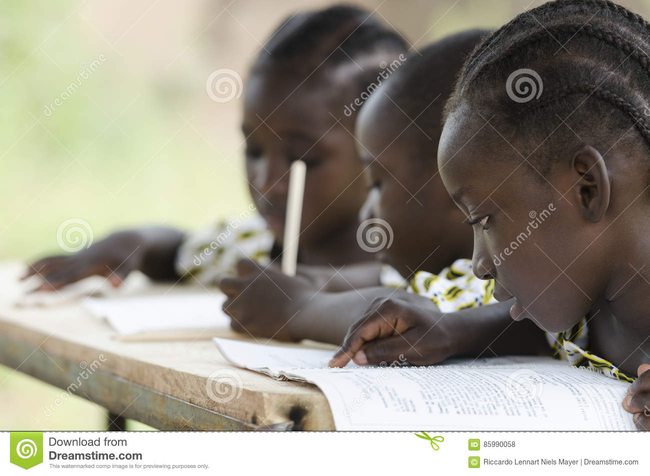 Three African children learning at school outdoors