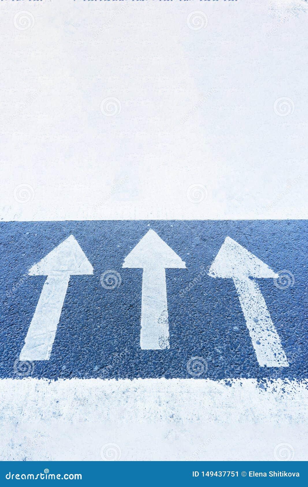 Three arrows on the blue surface of the asphalt point up, forward.