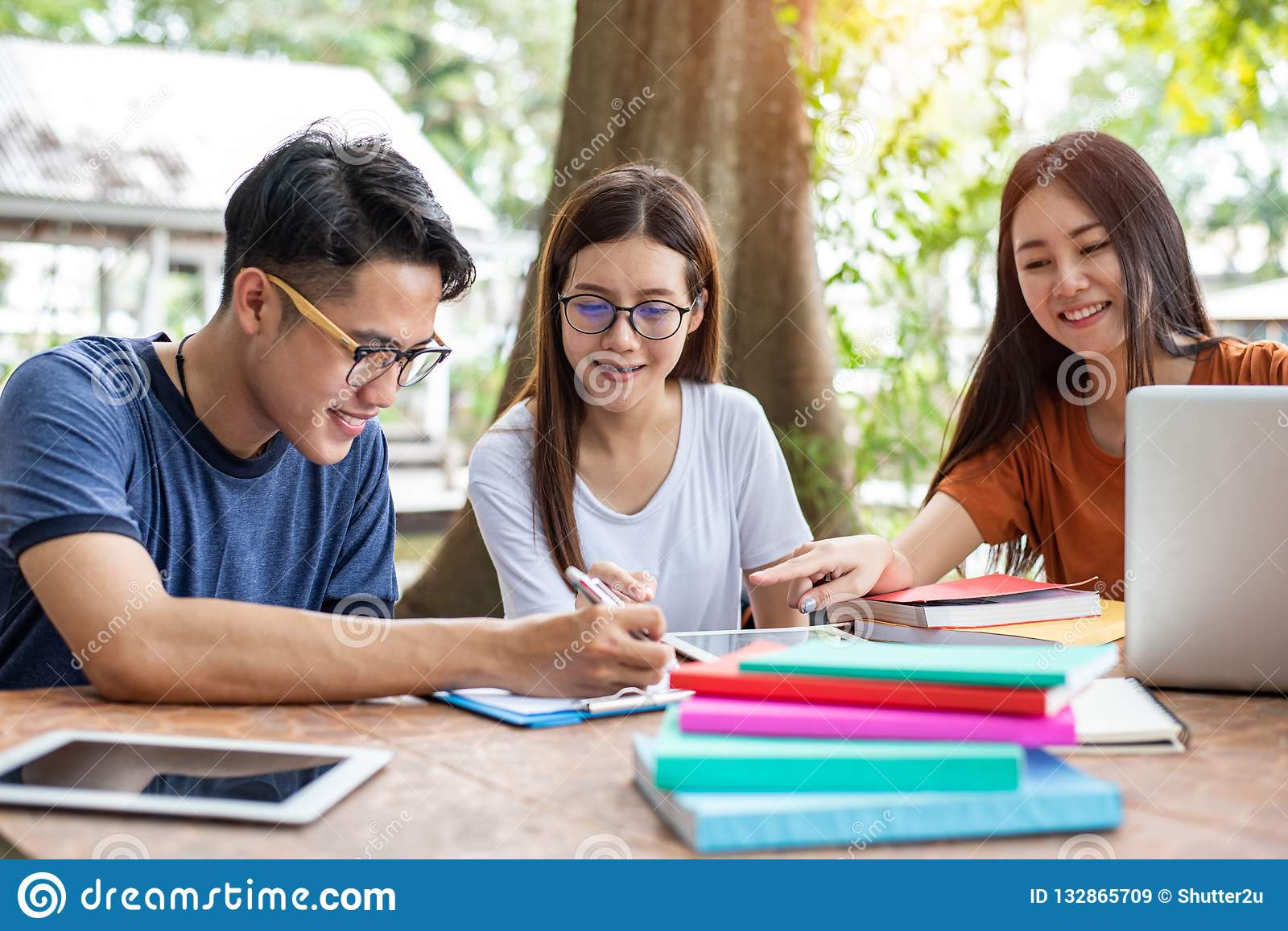 Three Asian young campus students enjoy tutoring and reading boo