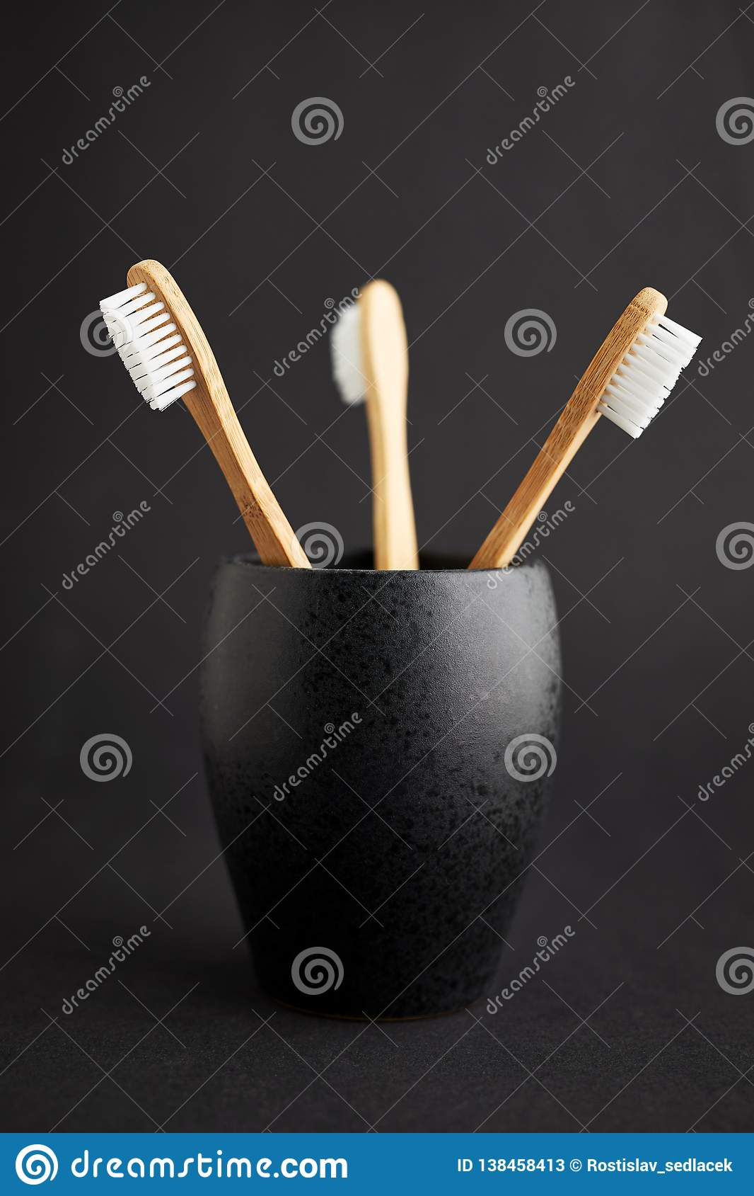 Three bamboo toothbrushes in a black glass