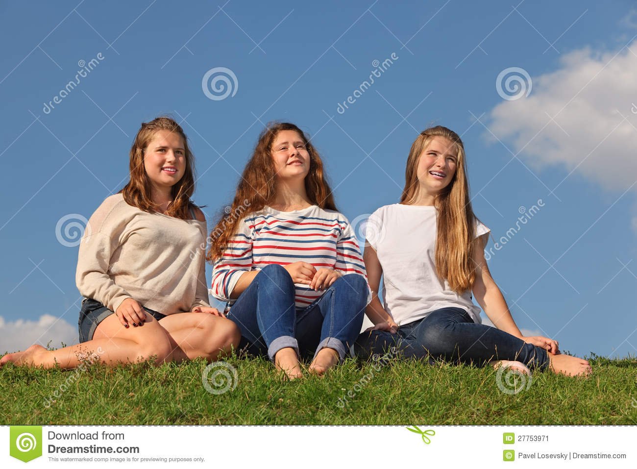 ... barefoot girls sit at green grass and look into distance at sunny day