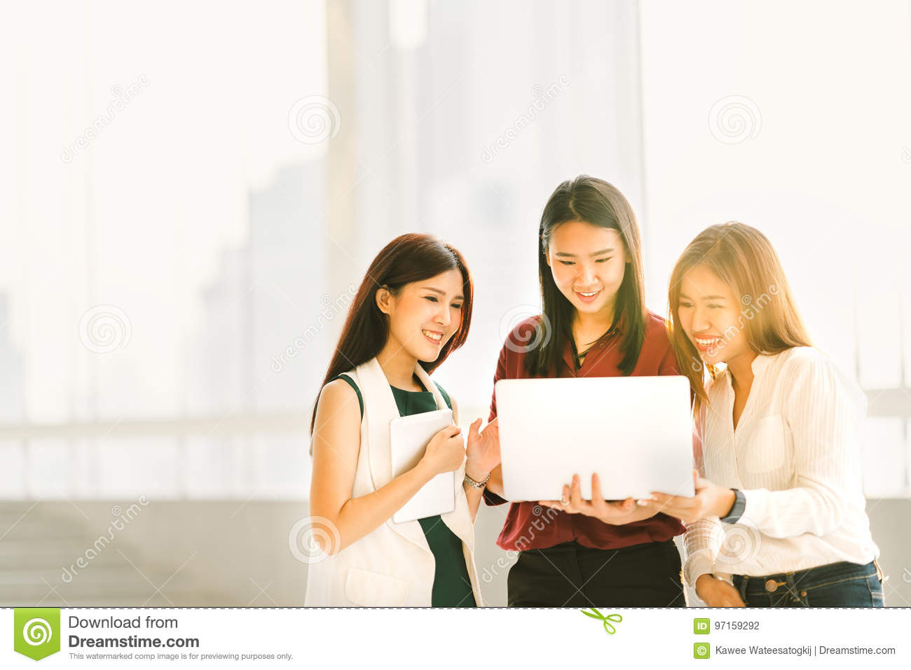 Three beautiful Asian girls on casual business meeting with laptop notebook and digital tablet at sunset