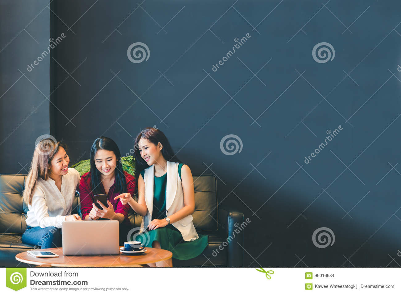 Three beautiful Asian girls using smartphone and laptop, chatting on sofa together at cafe with copy space