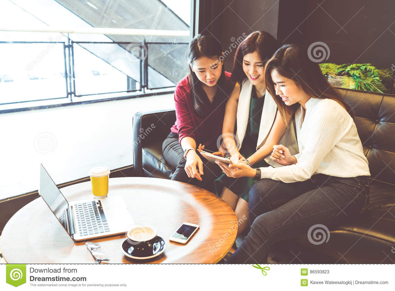 Three beautiful Asian girls using smartphone and laptop, chatting on sofa at cafe