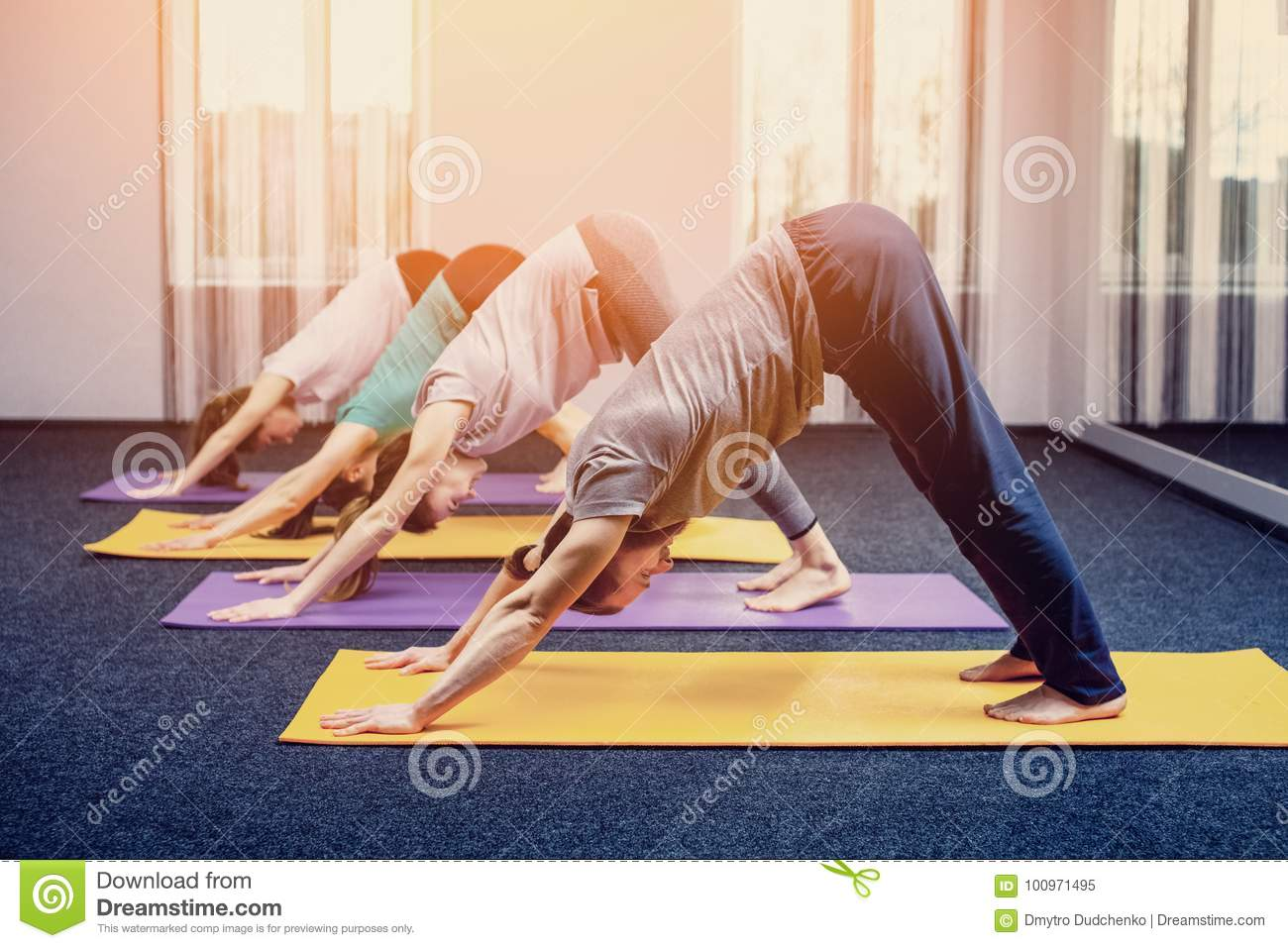 Three beautiful girls and man do yoga in the center of yoga and spa.
