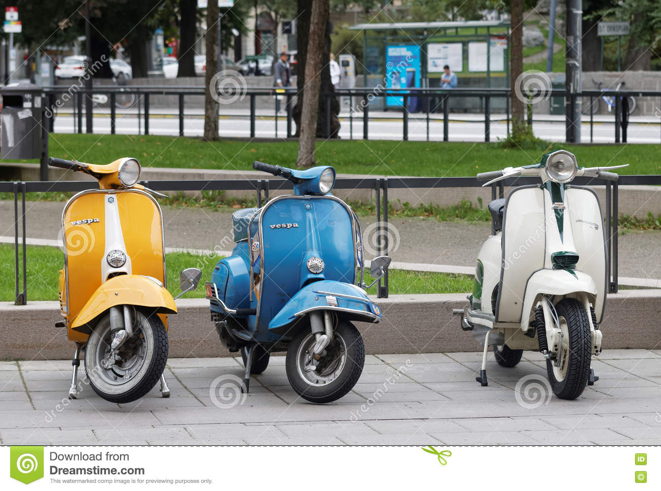 Three Beautiful Yellow, Blue And White Retro Vespa Scooters Park
