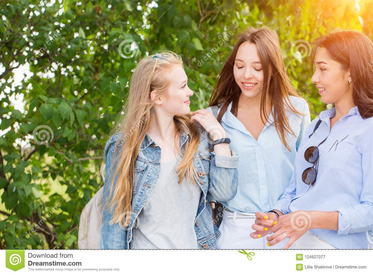 Three beautiful young girls students walking in the Park, talking and smiling against the trees