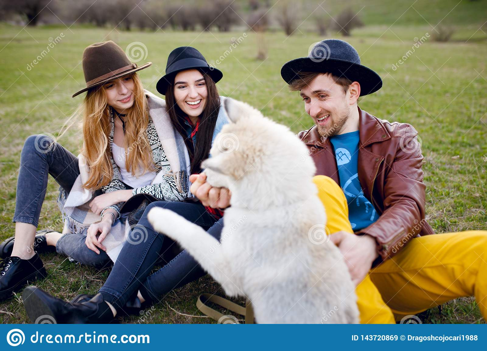 A three beautiful young stylish friends spend time outdoors together with their husky dog sitting on green grass.