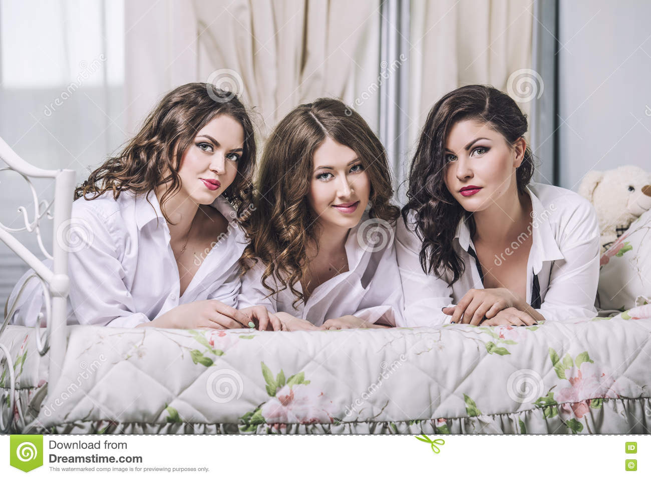 Three beautiful young women friends chatting in the bedroom in