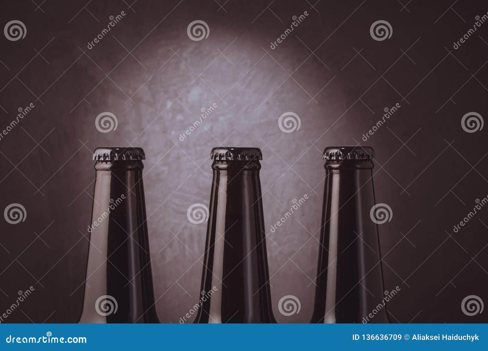 three black bottles of beer on a dark background with light/ three black bottles of beer on a dark background with light