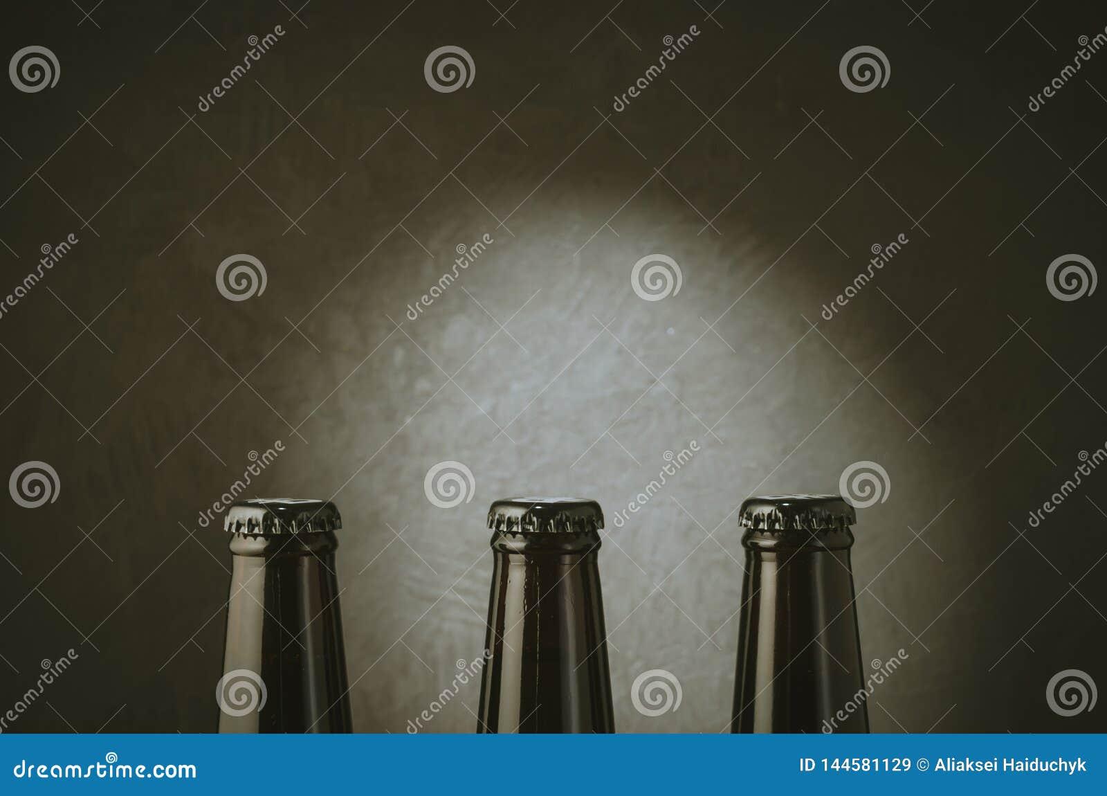 three black bottles of beer on a dark background with light/three black bottles of beer on a dark background with light. Copy