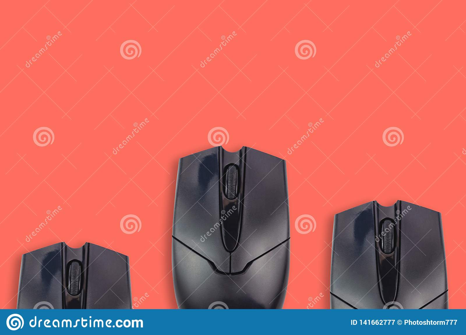 Three black plastic optical computer mouses on office table coral color. Top view. Copy space for your text