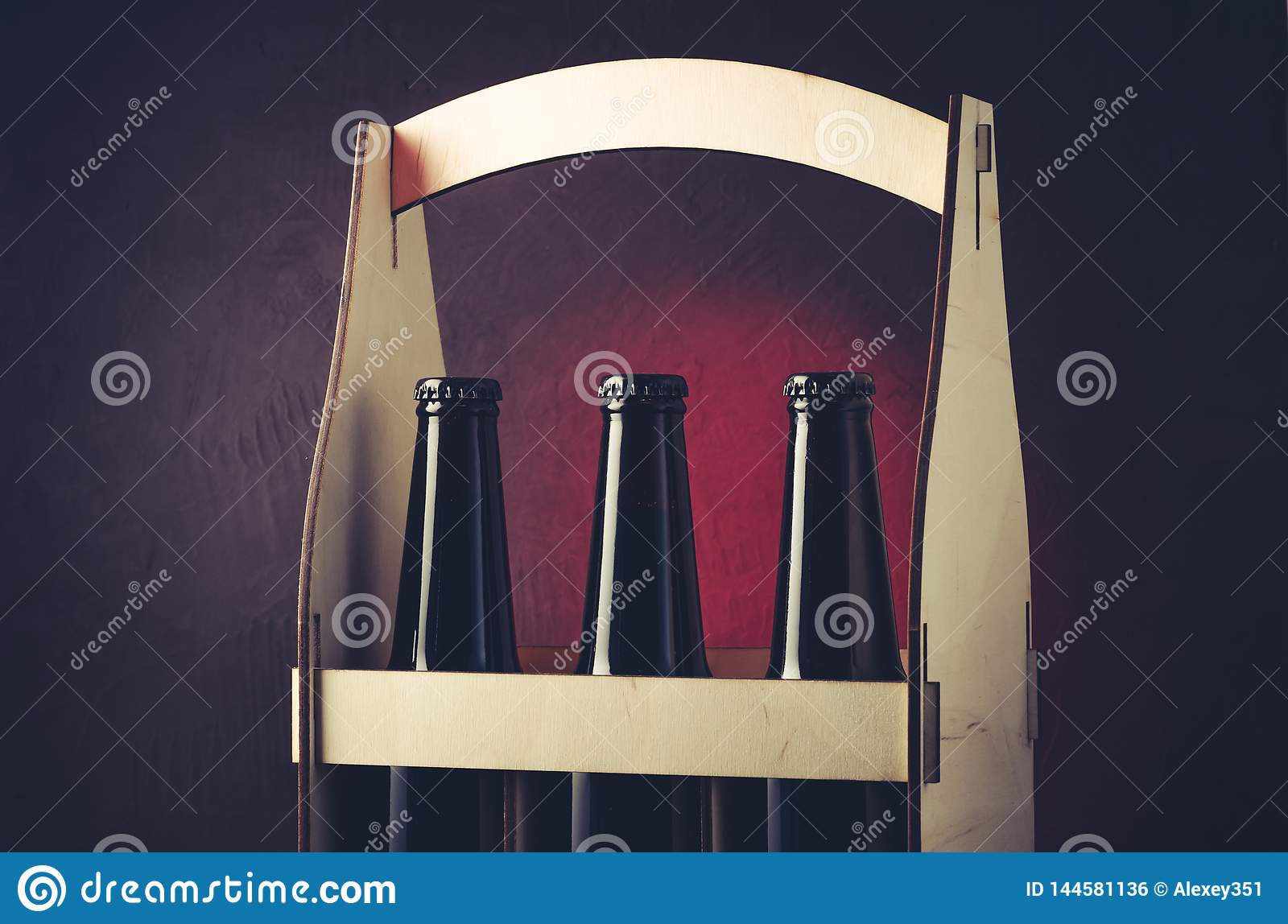 three bottles of beer in a wooden box/three bottles of beer in a wooden box on a red light background. Selective focus