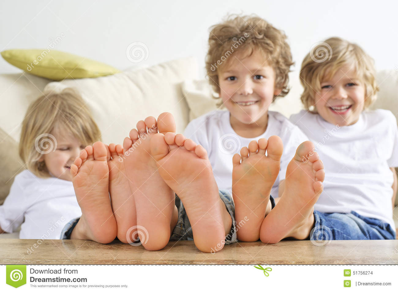 Three Boys With Bare Feet On Table