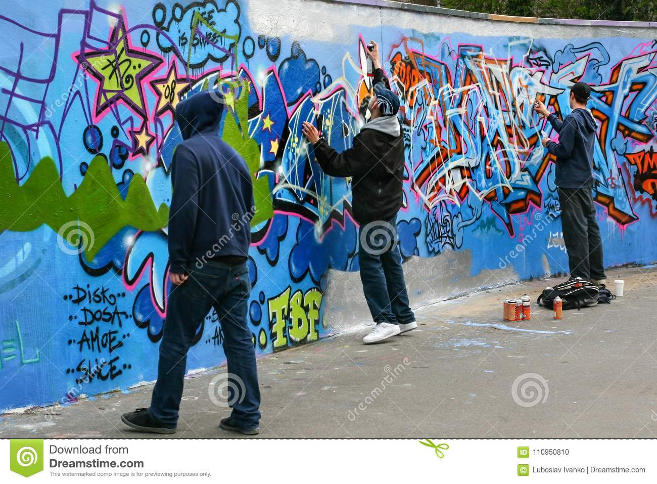 Three boys painting grafitti