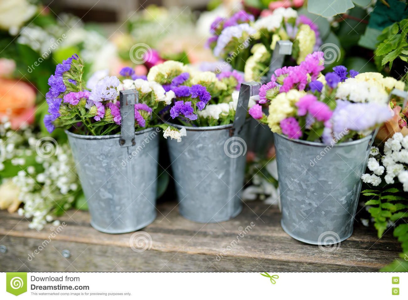 Three Buckets Of Beautiful Purple And White Flowers Prepared For