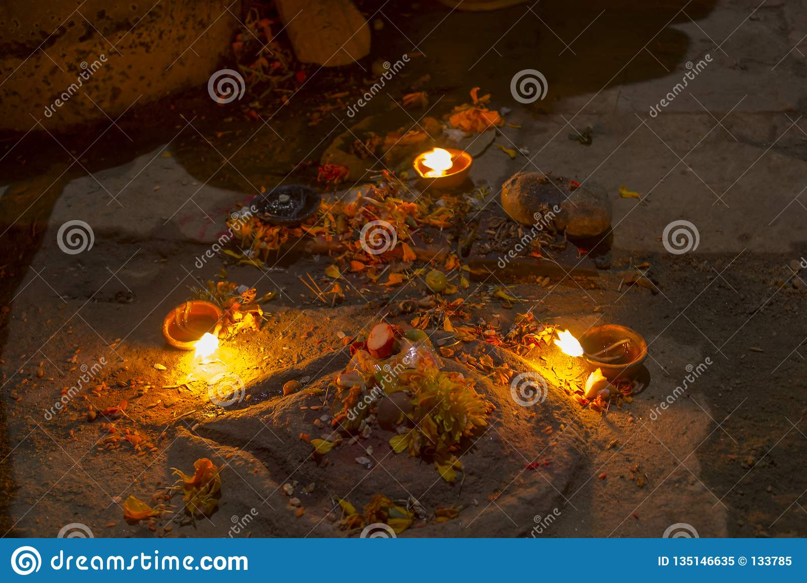 A Three Burning Candles Near The Ancient Altar With Flowers