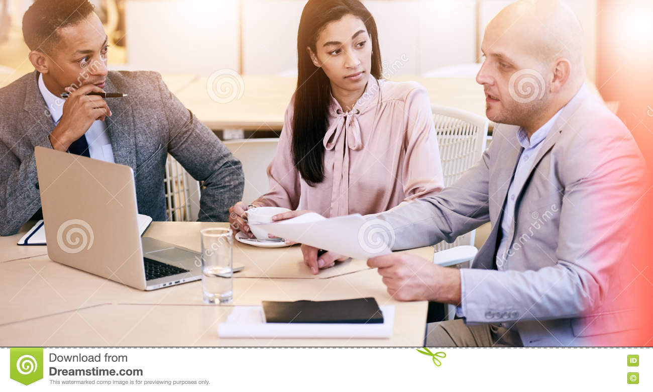 Three business executives communicating during meeting in conference room