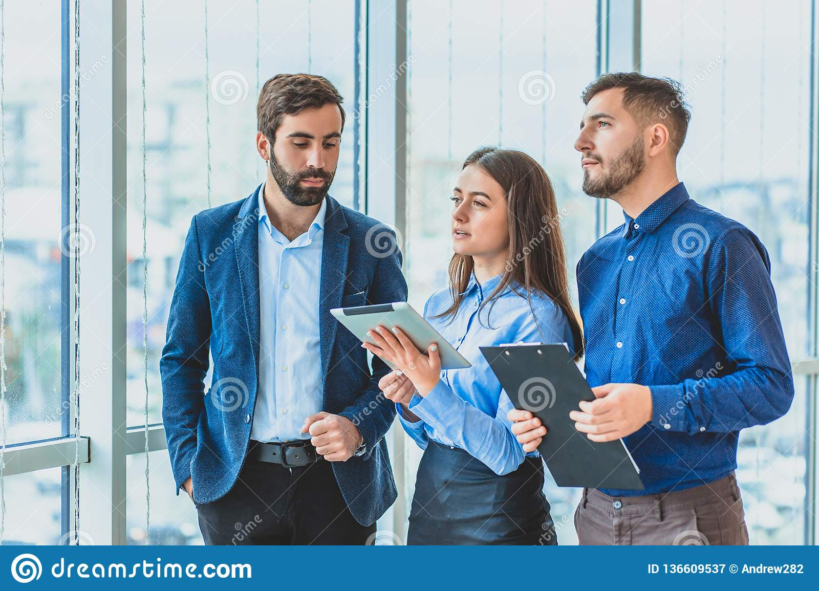 f4606a073e3b Three businessmen are in the office dressed in business clothes. During  this one in the hands of a folder with documents