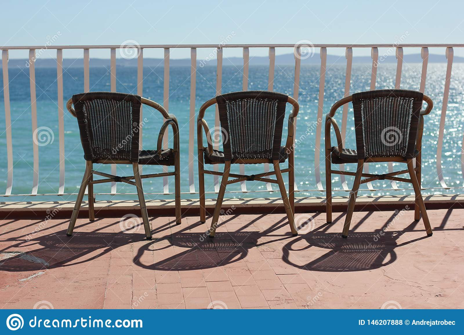 Three chairs in terace above colorful adriatic sea