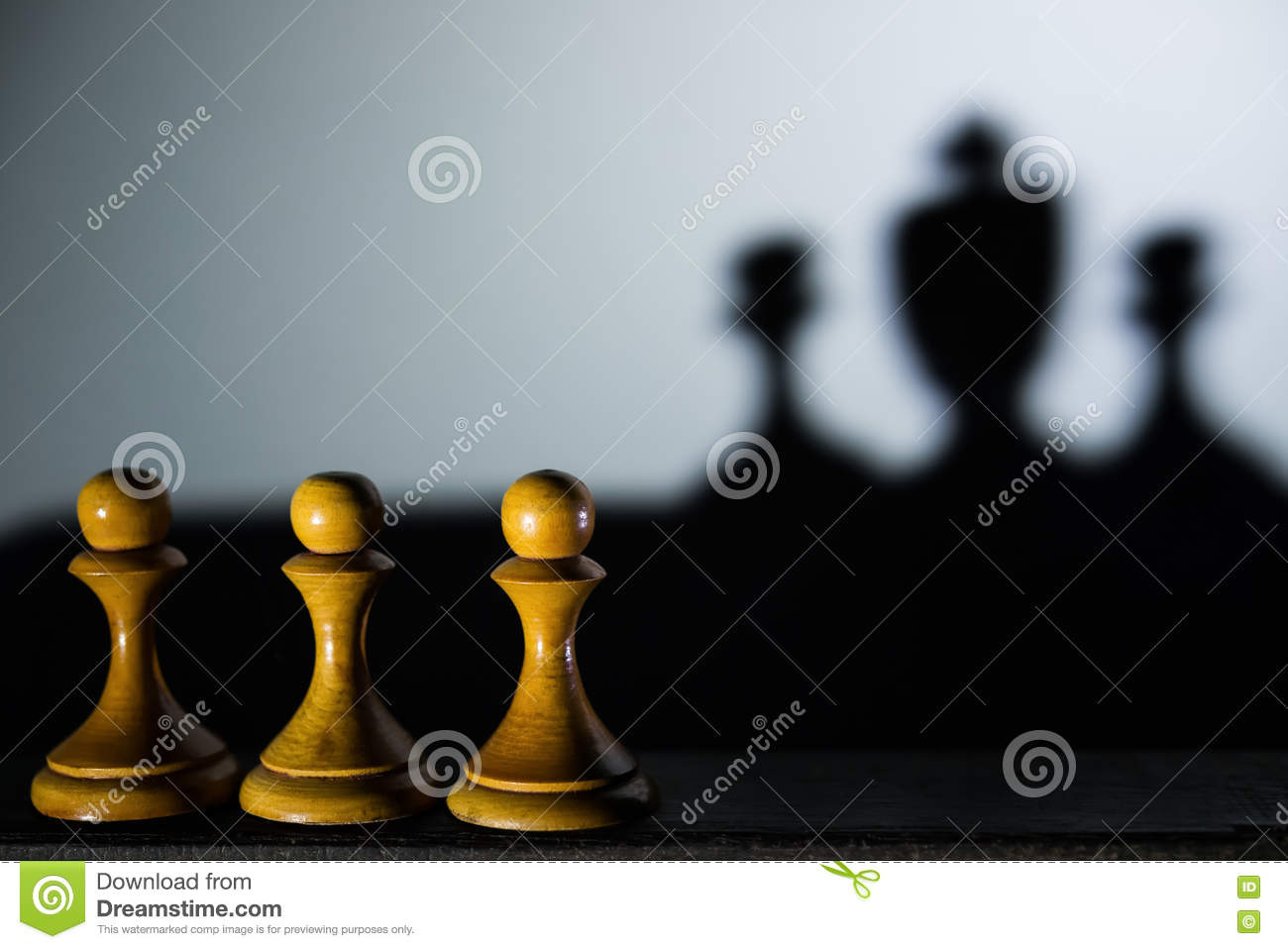 Three chess pawn with one casting a king piece shadow in dark concept of strength & aspirations