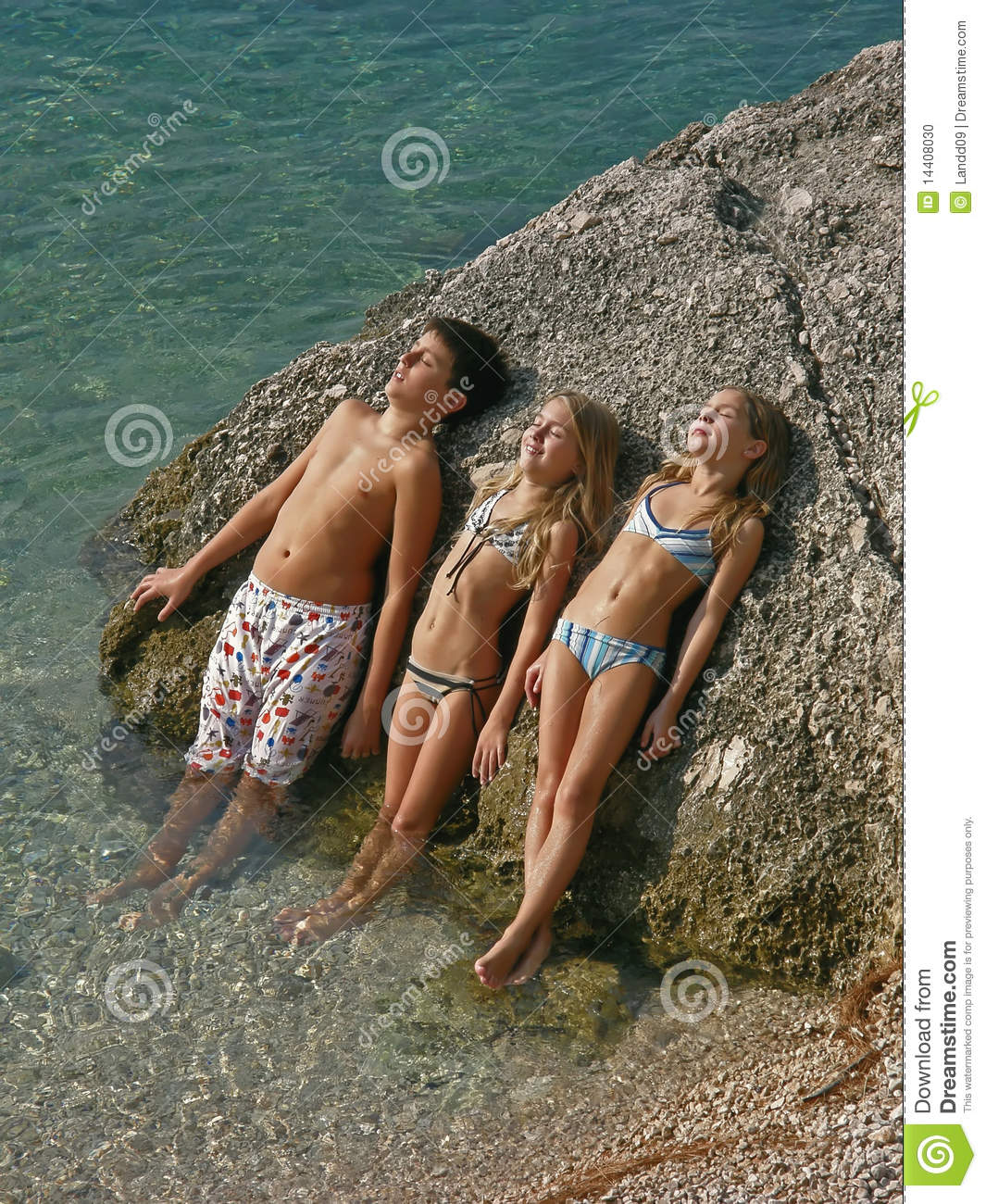 Three children bror and sister lie on a rock in Adriatic sea