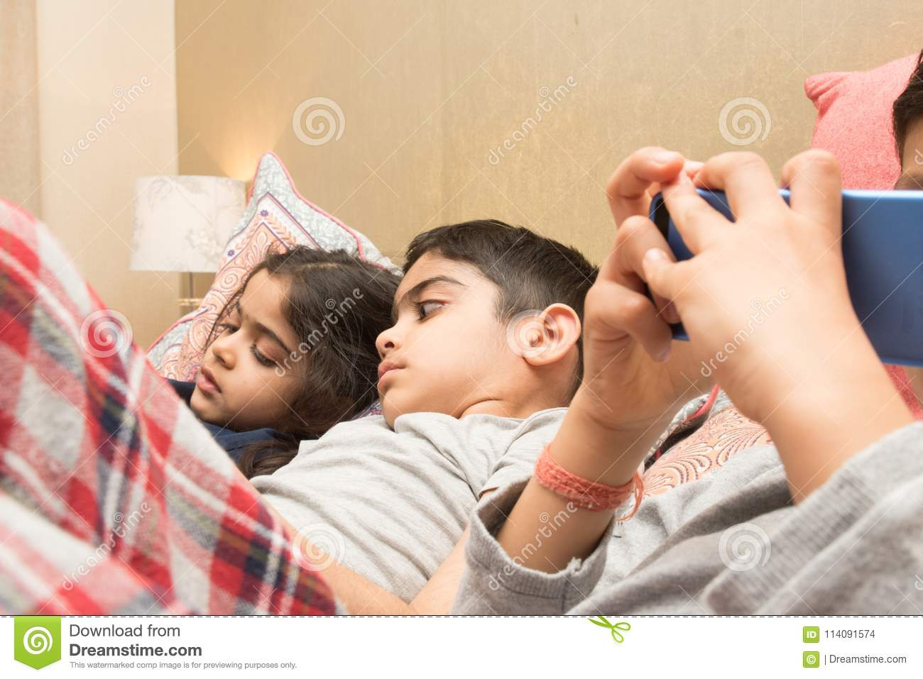 Three children with their electronic gadgets at bedtime.