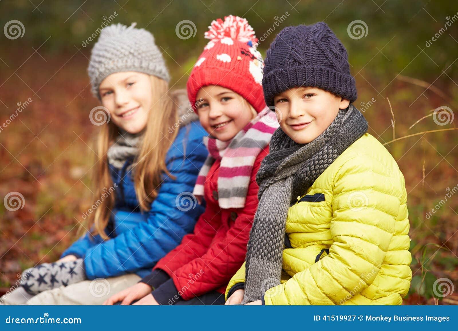 Three Children On Walk Through Winter Woodland