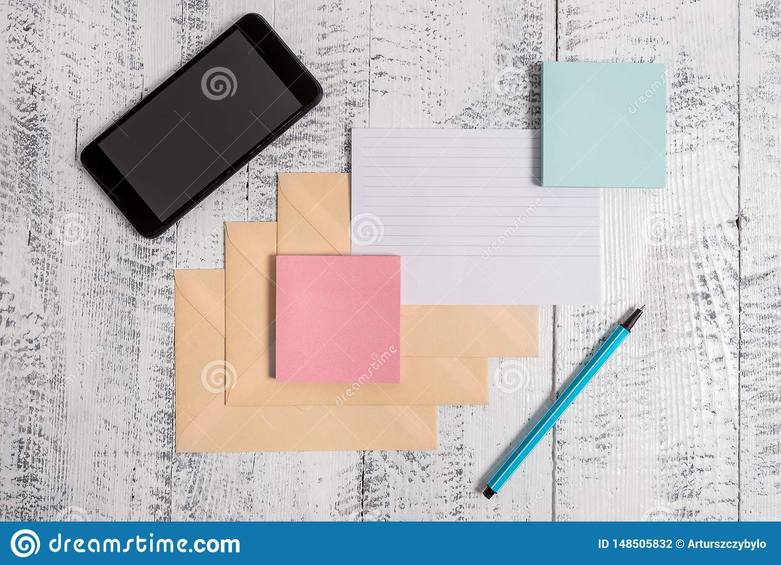 Three closed rectangular colored envelope ruled paper sheet smartphone sticky note pads marker lying wooden retro
