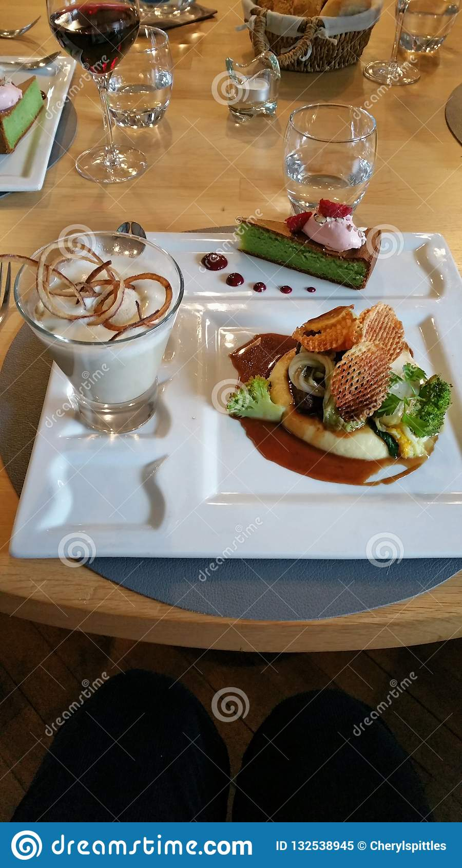 Lo Ng At A Restaurant Table Setting With Three Course Meal Served On White Square Porcelain Plate Containing Soup In Tall Glmain Course On Right And