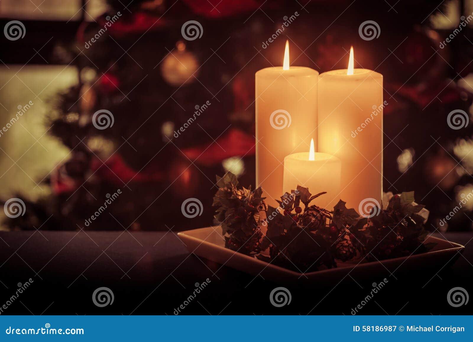 Three Cream Candles Burn Before Festive Tree Stock Photo