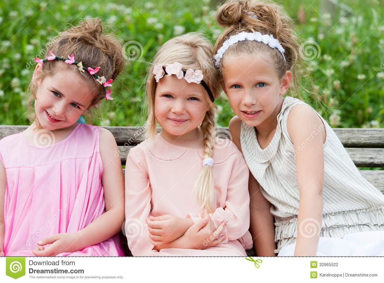 Three Cute Girl Friends Sitting Together On Wooden Bench