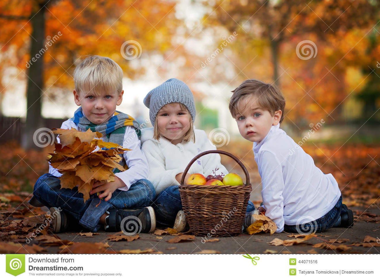 three cute kids in the park, with leaves and basket of fruits stock
