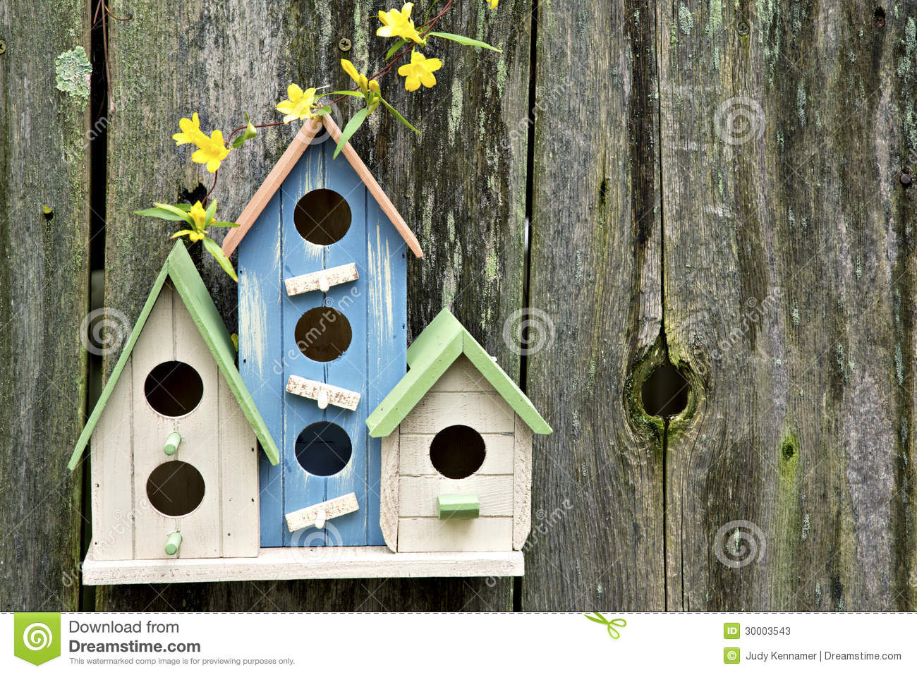 Three cute little birdhouses on wooden fence with flowers for Different types of birdhouses