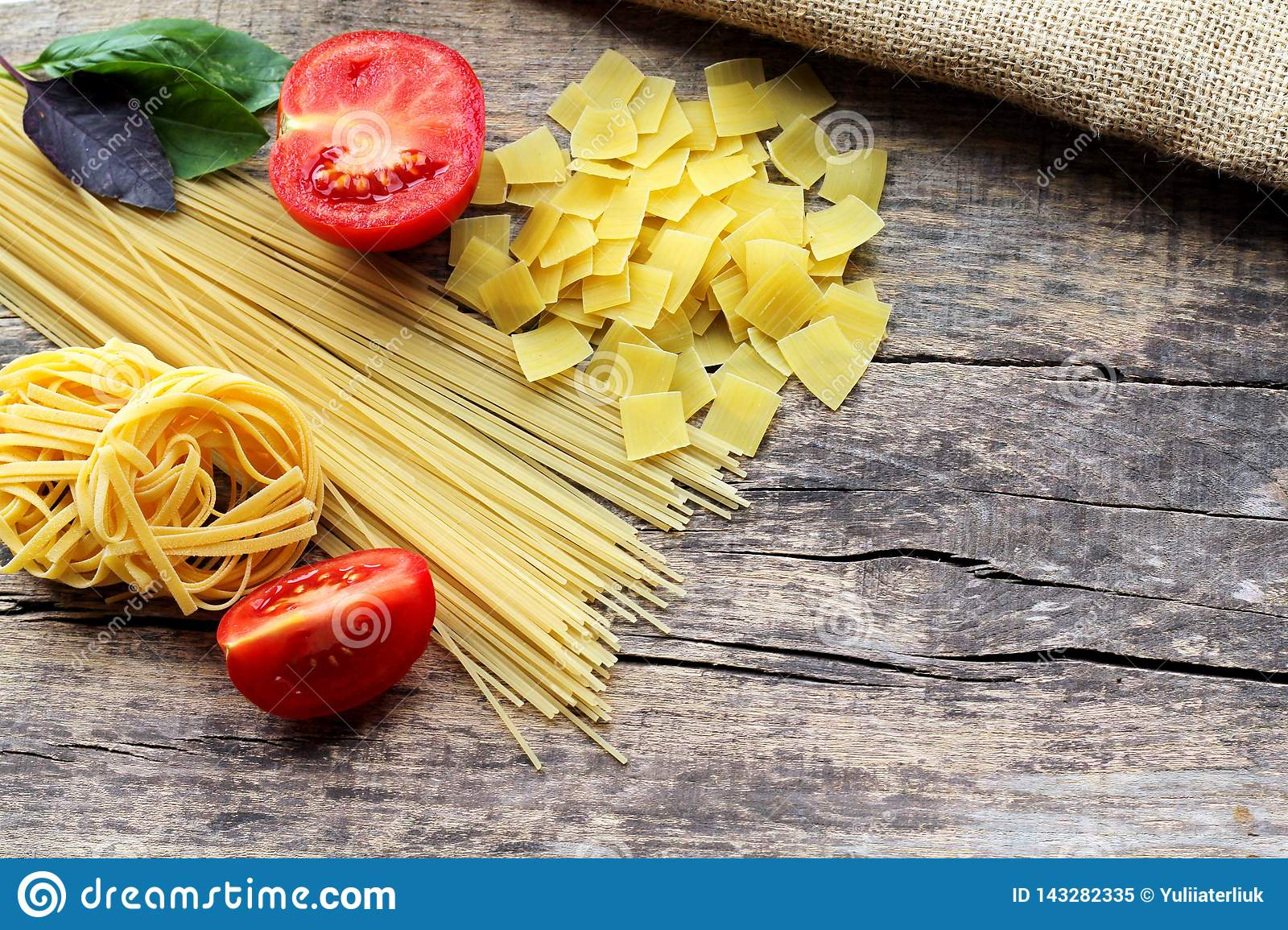 Three different types of pasta with fresh purple and green basil and red tomatoes on a wooden background with a place for text