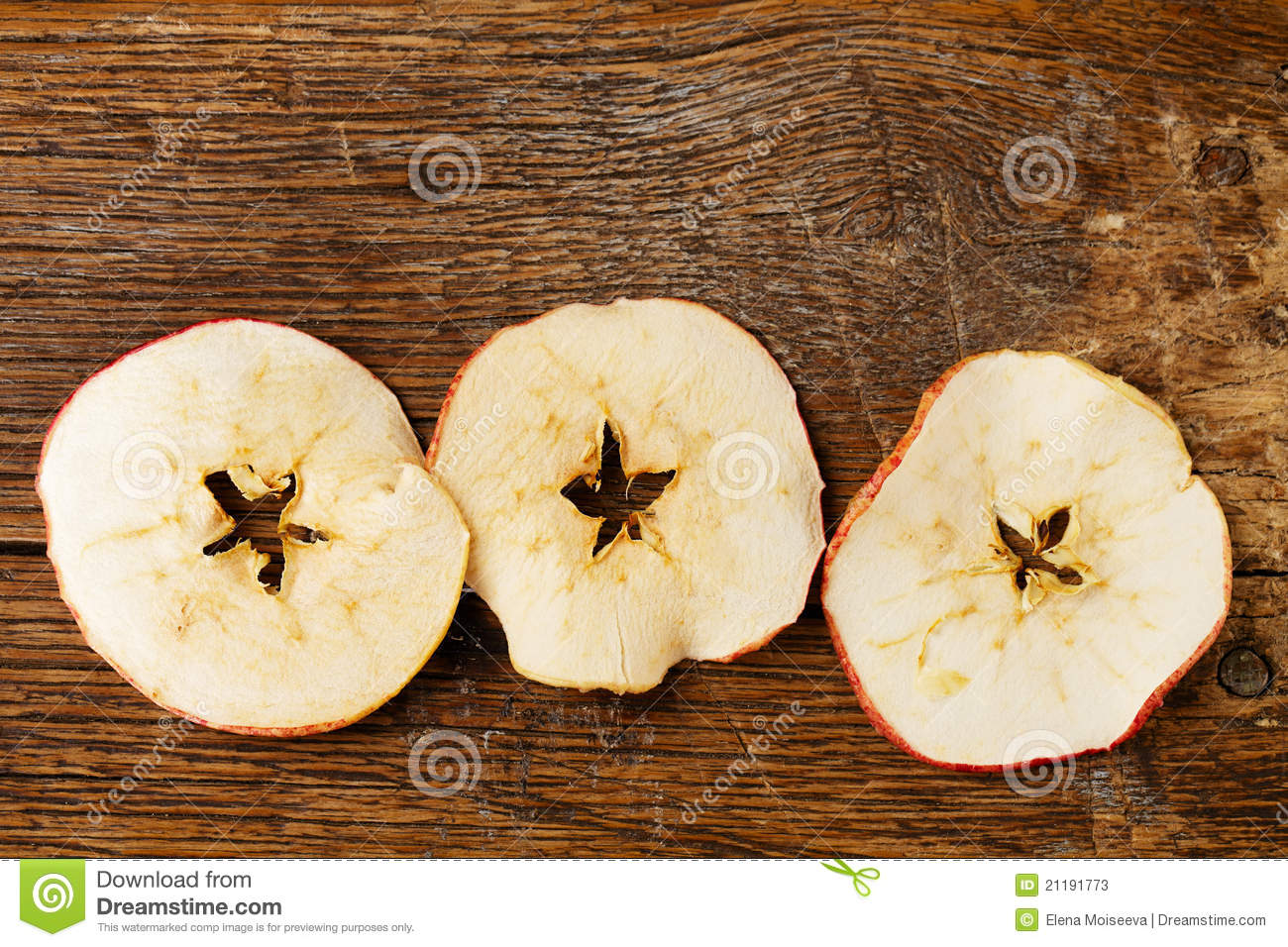 Three dried apples slices on old wooden table