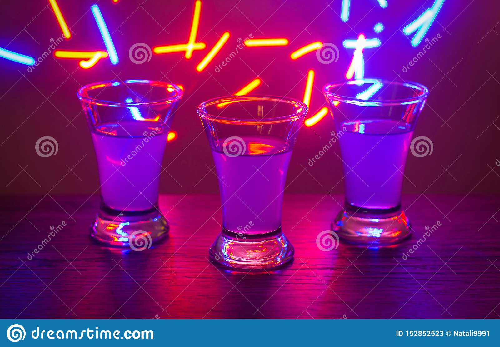 Three drinks at the party. Three shots with cocktails at the bar. Liquor, vodka, fresh. Shining on a colored background. Night clu